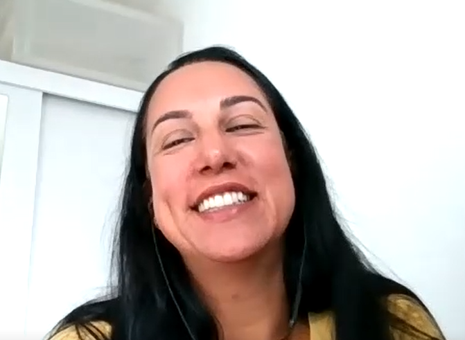 Foto de Catharina, uma mulher branca, de cabelos escuros e longos. Na imagem ela está sorrindo e veste uma camiseta amarela.