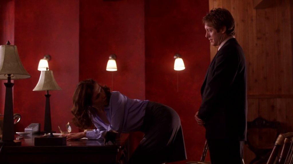 Lee Holloway bends over the desk and looks over her shoulder at Mr Grey