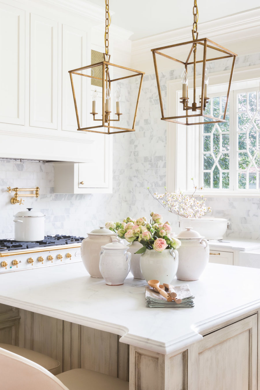 light beige kitchen island is surrounded by white shaker cabinets, white marble countertops and sits underneath two vintage gold pendant llights