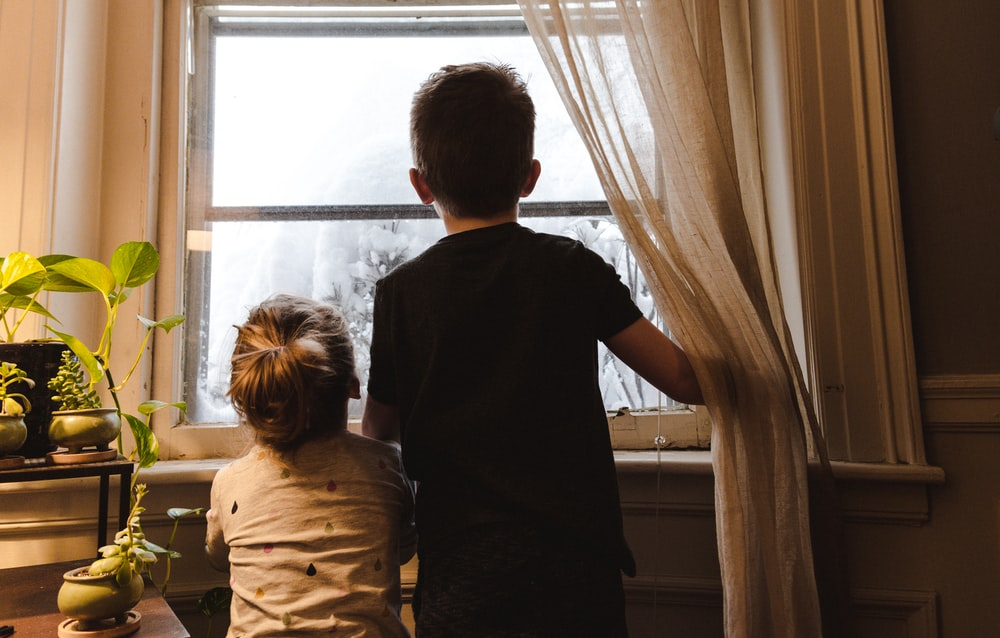 boy and girl standing near window looking outside