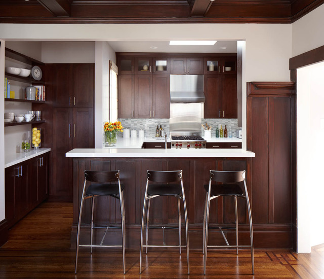 one of the best cabinet colors for 2020 is espresso. this photo features a kitchen fitted with rich espresso shaker cabinets, white countertops and wood floors