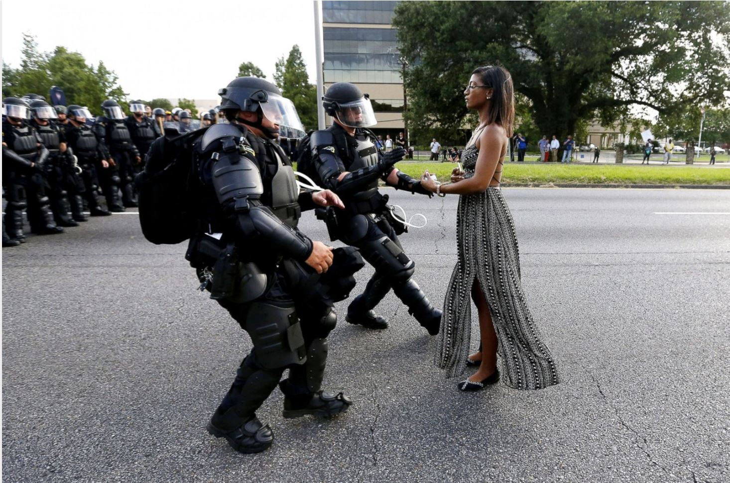 """[Ieshia Evans being detained by law enforcement in Baton Rouge, Louisiana on July 9, 2016, during a protest against police brutality following the murder of Alton Sterling. Source: ABC News article """"Black Lives Matter: A movement in photos""""]"""