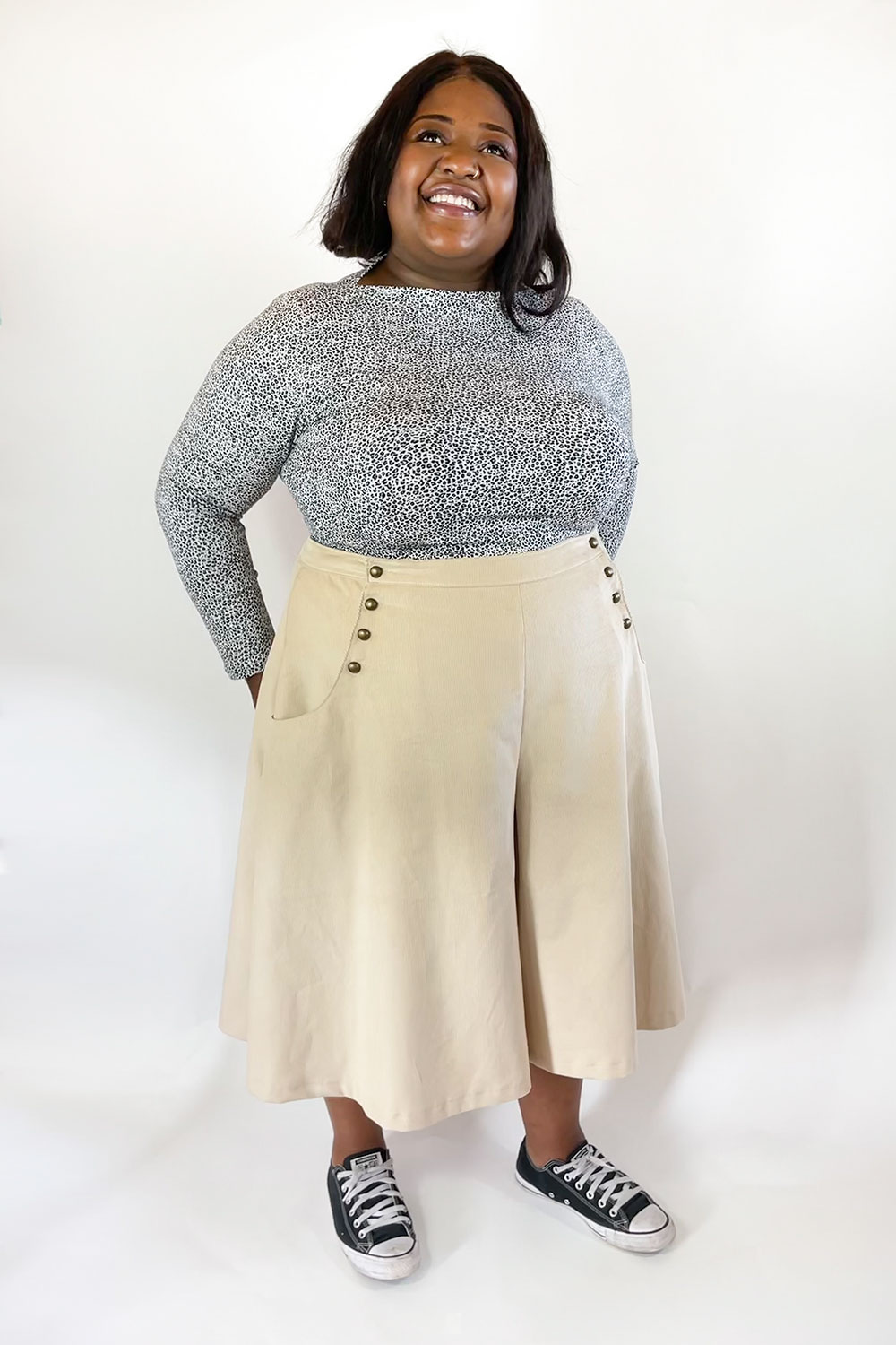Image of black woman in black and white spotted knit top and tan colored sailor-style culottes.