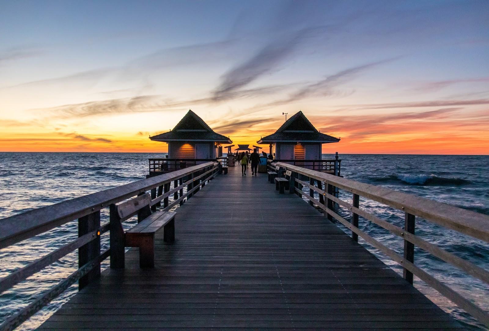 wooden pier atop blue wavy ocean during sunset in naples florida