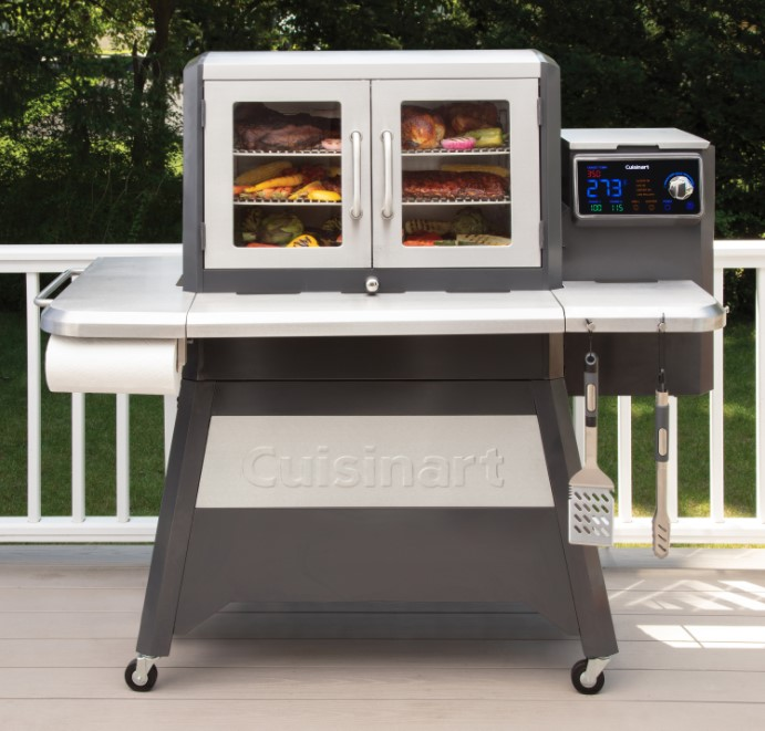 An image of Cuisinart Clermont pellet grill on an outdoor patio with different foods in the grill chamber.