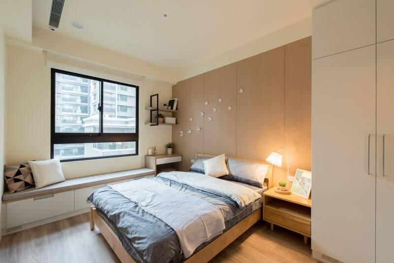 臥室設計將主牆面與木地板色系相呼應並搭配上淺色梣木床架與床頭櫃完美地適切臥室空間