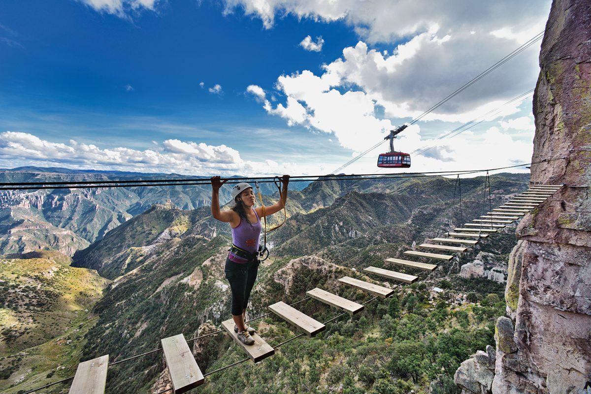 Un hombre en al aire con una montaña al fondo  Descripción generada automáticamente con confianza baja