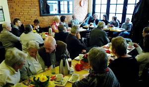 Frauen und Männer an feierlich gedeckten Tischen.