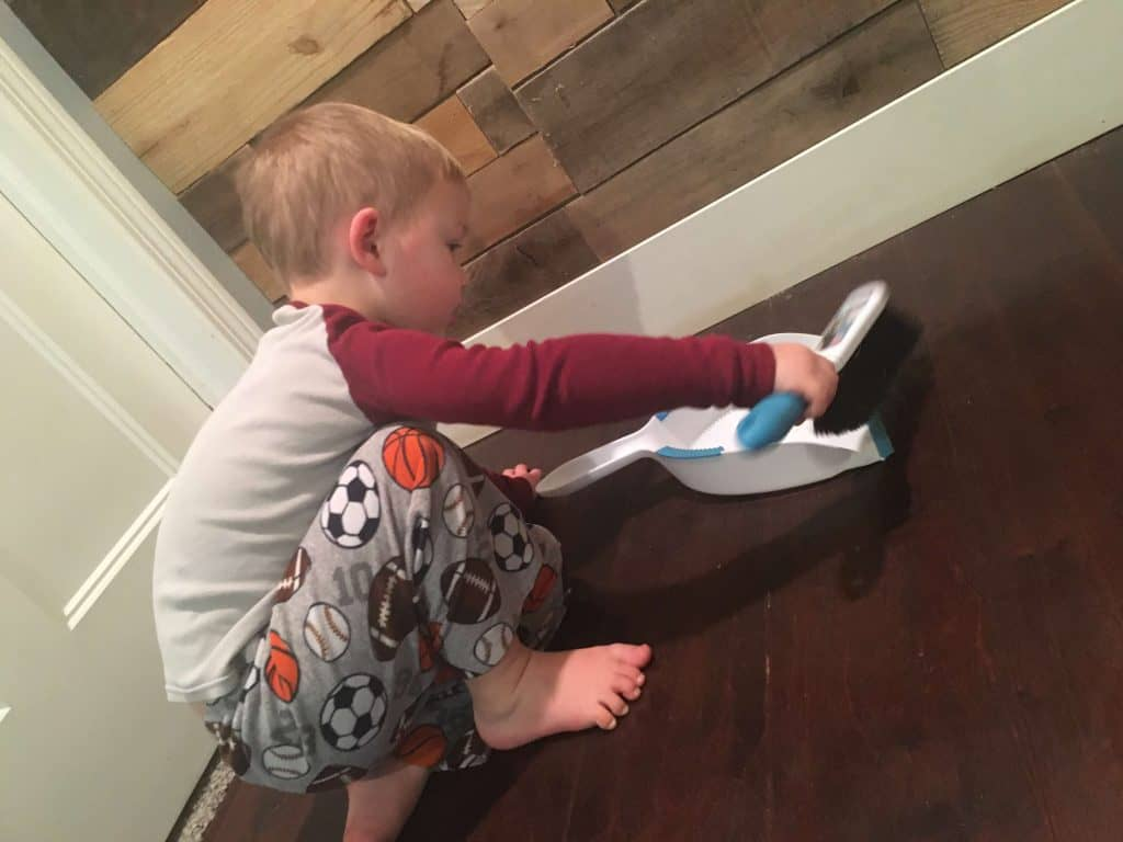 Age appropriate chores for toddlers: a picture of a toddler sweeping with a handheld broom and dustpan