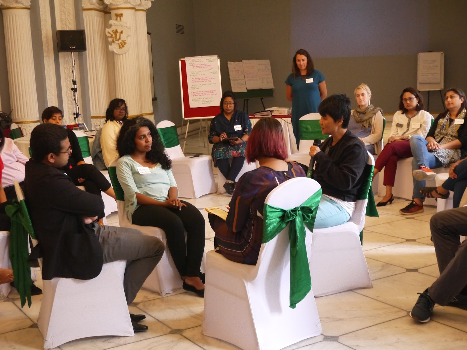 Four Members gather in the centre of the room in a circle with their backs facing the rest of the larger group who sits in a big circle listening to the discussion. This style of discussion is called fishbowl