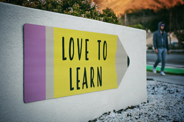A white short wall with a large image stuck on it of a big yellow pencil with a purple eraser and the words LOVE TO LEARN written on it.