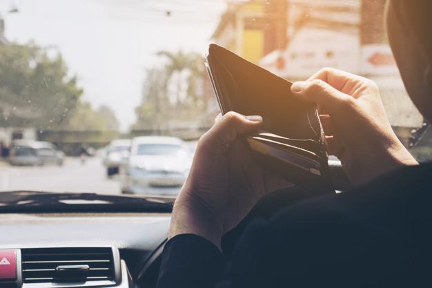 Pessoa segurando a carteira dentro do carro e verificando quanto ganha um uber.