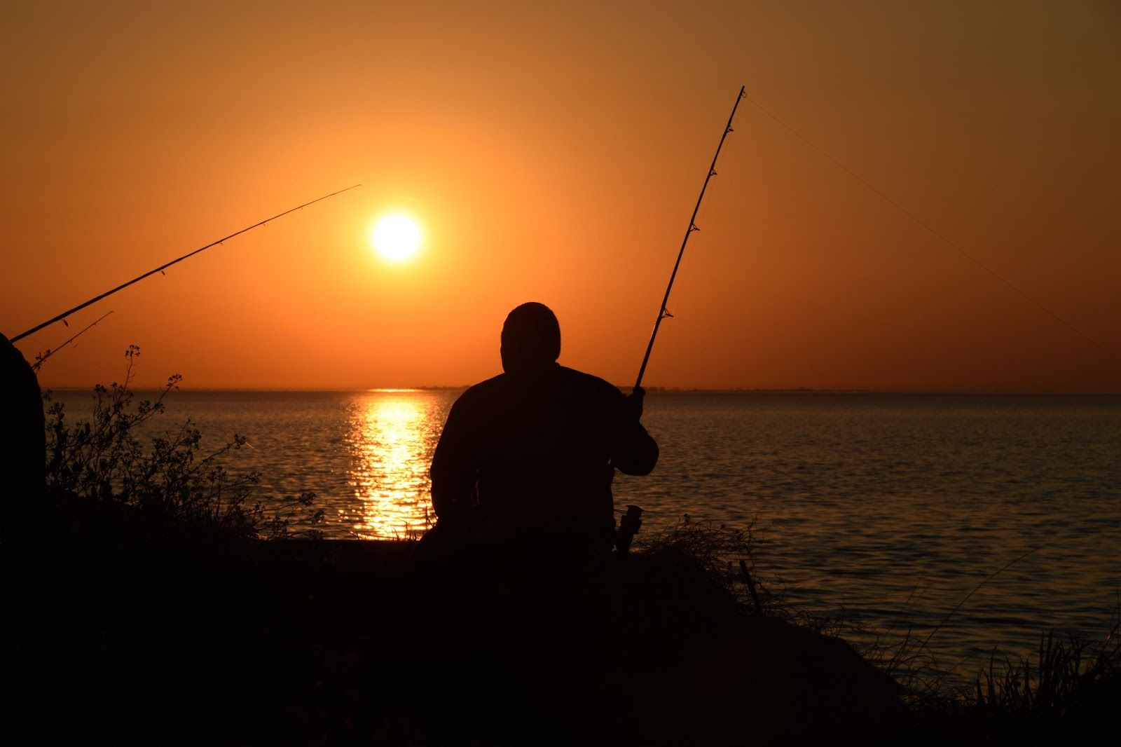 man fishing by the sunset