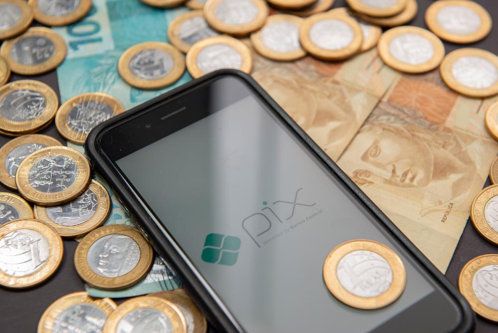 Celular com imagem do PIX em cima de notas de dinheiro e moedas