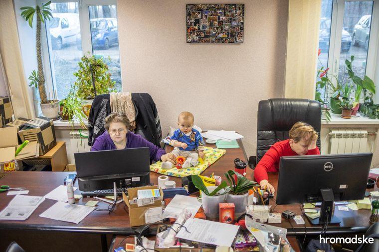 Нина Терехова держит маленькую Соломию за ногу, страхуя от падения и одновременно работая за компьютером в офисе БФ «Свои», 23 марта 2021 года