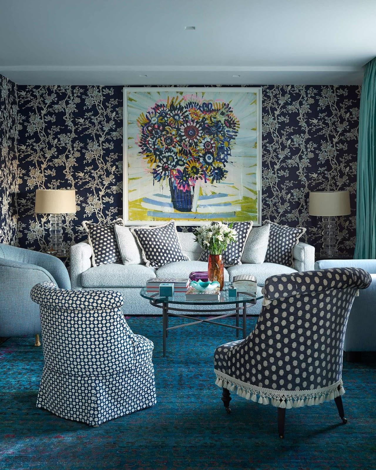 Sala com papel de parede, poltronas com estampa de bolinhas, tapete azul, sofá com almofadas.