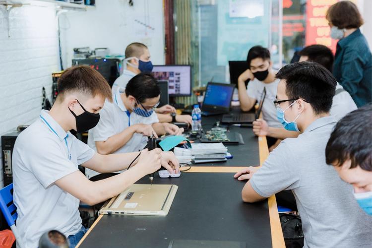 Kỹ thuật viên và khách hàng tại trung tâm Sửa chữa Laptop 24h