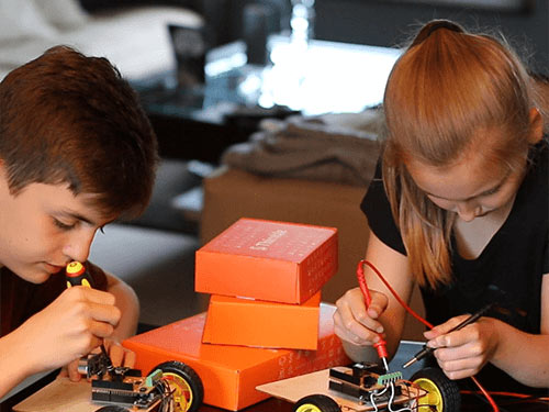 Two children concentrate as they work to assemble the WIFI Robot from one of Thimble's STEM kits at a table. The table is covered in orange Thimble delivery boxes.