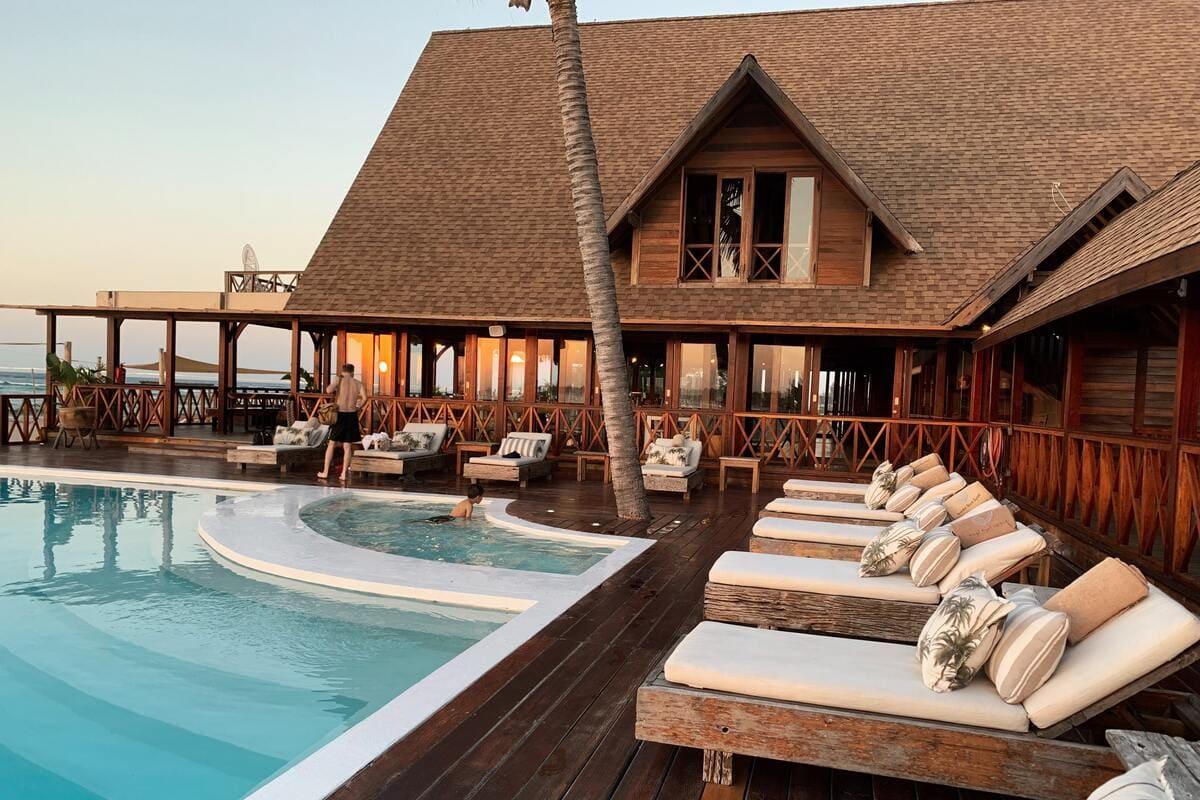 Una piscina di un hotel con vista mare costeggiata da diversi lettini per prendere il sole