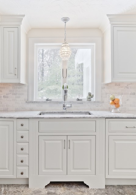 bright white kitchen with white inset cabinets, silver hardware, white stone backsplash and small chandelier over the sink