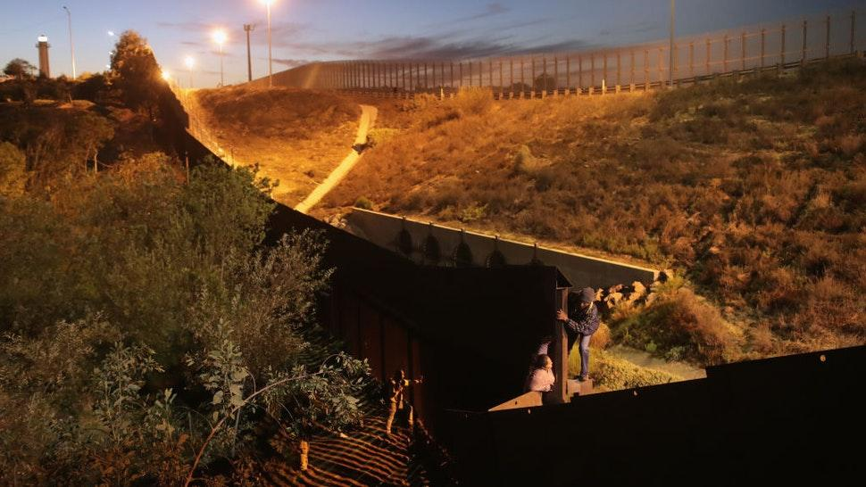 Members of the migrant caravan climb over the U.S.-Mexico border fence on December 3, 2018 from Tijuana, Mexico.