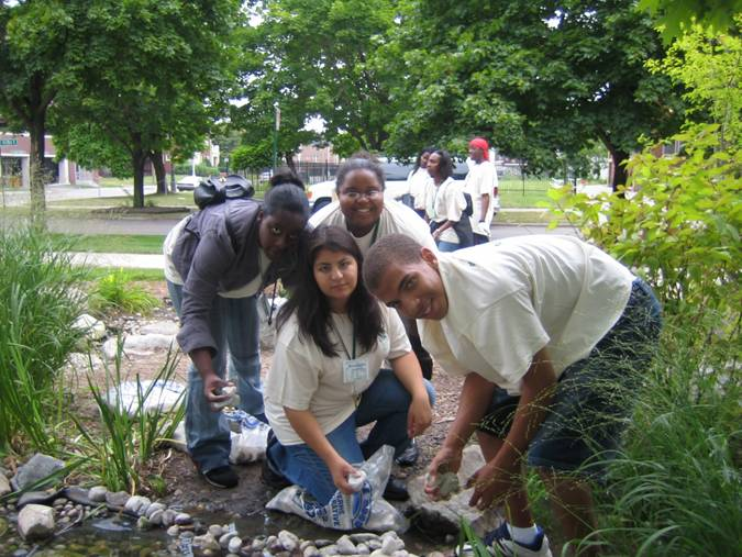 A group of young adults clean up a polluted natural area.