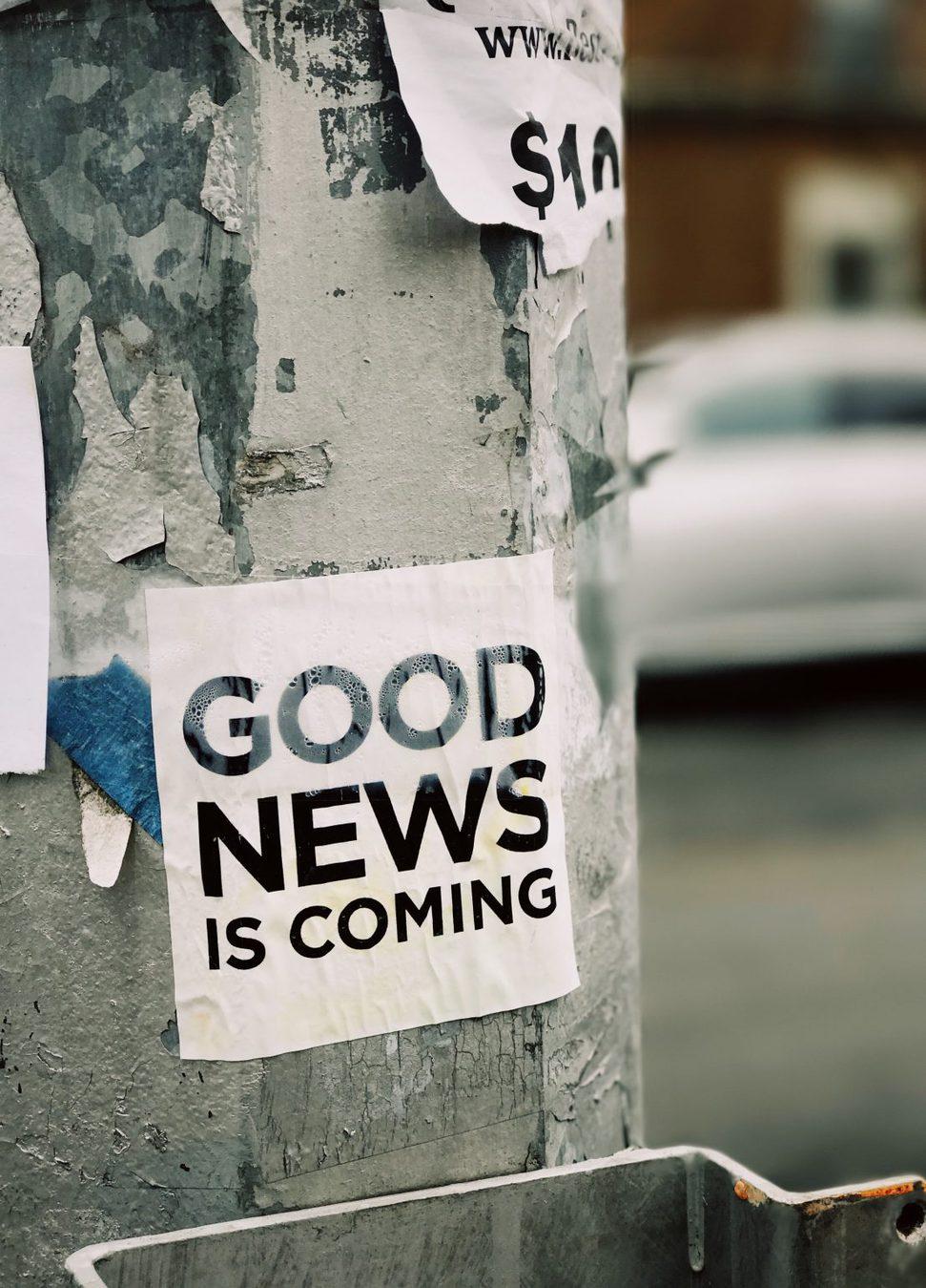 """Plakat na murze z napisem """"good news is coming"""" (dobre wieści nadchodzą)"""