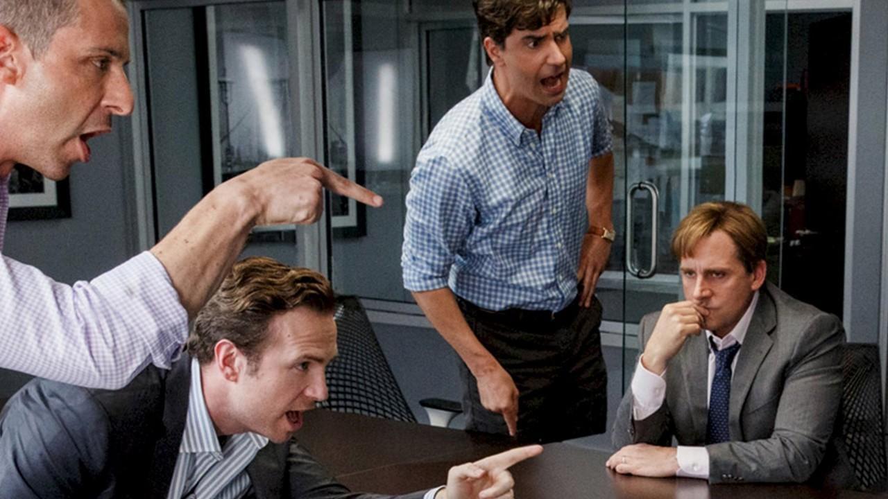 escritório com quatro homens de roupa social discutindo entre si
