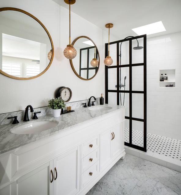 modern bathroom with white vanity, circular mirrors, brass hanging pendant lights, marble floor and black framed shower door