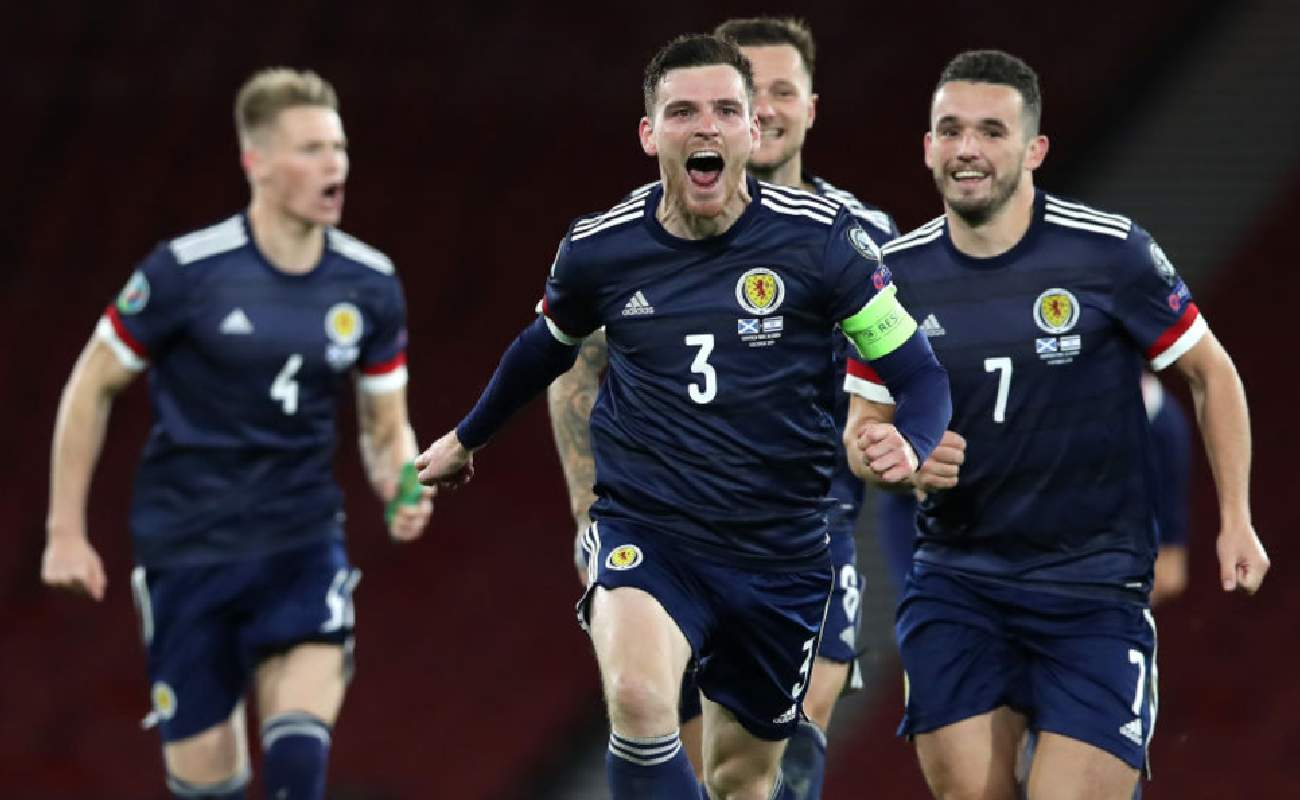 Alt: Andy Robertson and other Scottish players celebrate after winning a game - Photo by Ian MacNicol/Getty Images