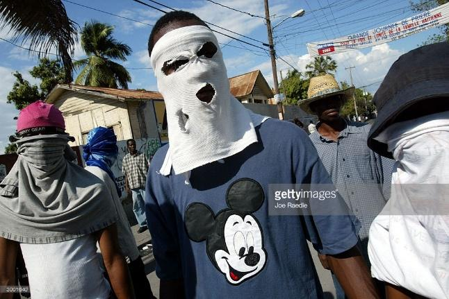 http://media.gettyimages.com/photos/haitians-wear-masks-during-a-demonstration-demanding-that-president-picture-id3001640