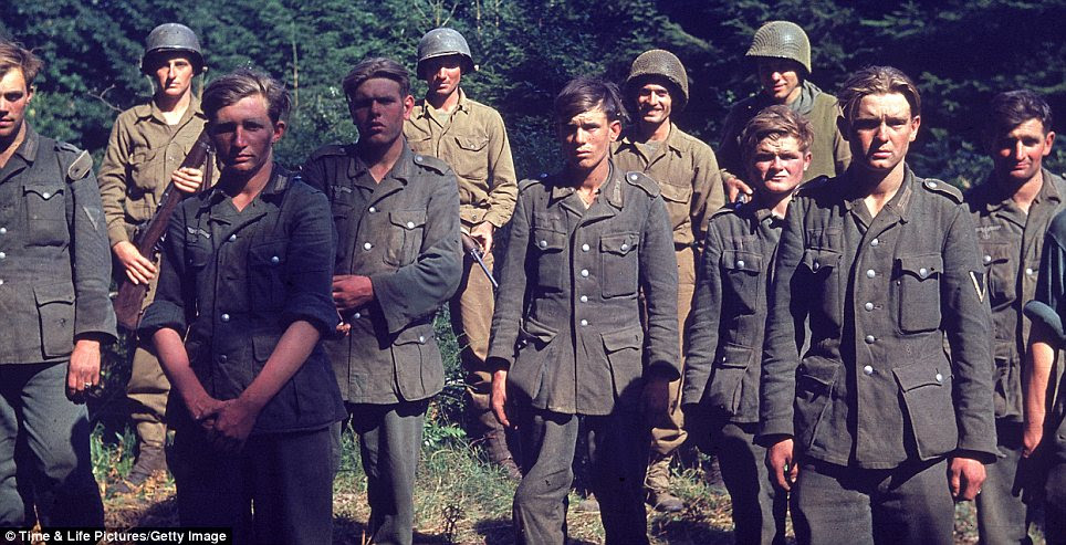 Prisoners: American troops stand guard behind German soldiers captured near the town of Le Gast during the Normandy invasion