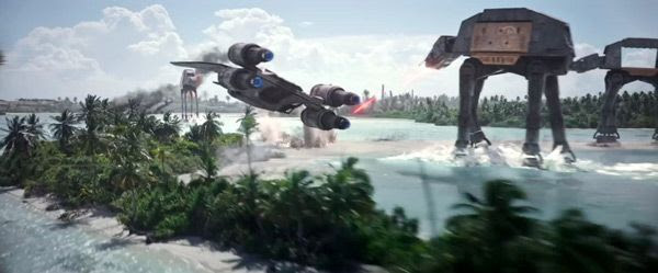 On the planet Scarif, the U-Wing starfighter flies past AT-ACT walkers as they strafe a beach in ROGUE ONE: A STAR WARS STORY.