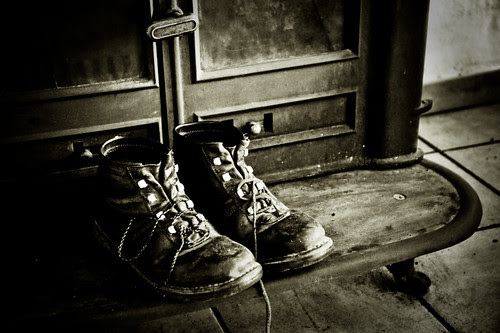 hiking boots warming by the wood stove