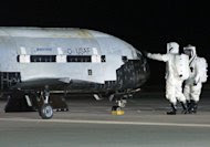 An X-37B robotic space plane sits on the Vandenberg Air Force base runway during post-landing operations on Dec. 3, 2010. Personnel in self-contained protective atmospheric suits conduct initial checks on the robot space vehicle after its landi