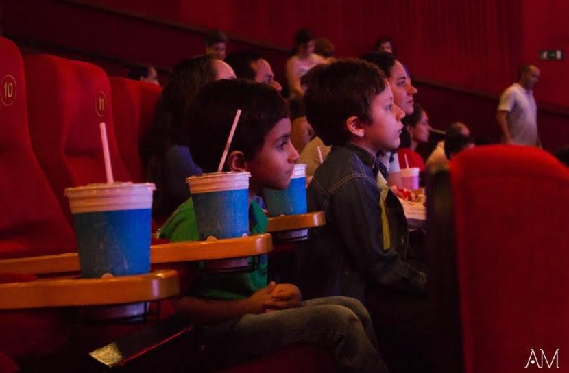 Foto de uma sala de cinema com duas crianças olhando em direção da tela.