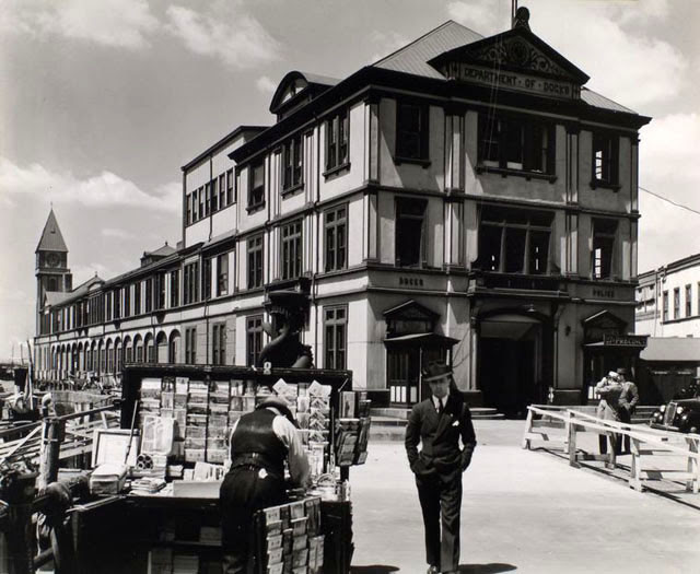 Department of Docks and Police Station, Pier A, North River, Manhattan. Long building wtih clock tower at far end housing Dept. of Docks and a Police station; man walks toward camera near newsstand in foreground.
