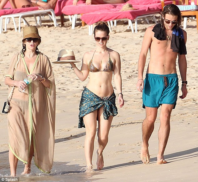 Stylish family: The London-born star threw on a snakeskin print string two-piece and a flattering sarong as she enjoyed a stroll down the beach with her mother and brother when the sun later came out