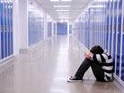 A boy sits with his head down in a school hallway.