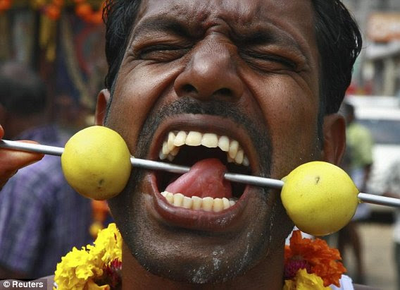 A Hindu devotee with a pierced tongue takes part in a procession during the Thaipusam festival