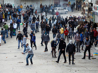 Palestinians throw stones towards Israeli troops during clashes that broke out after a rally in the West Bank city of Hebron to show solidarity with prisoners on hunger strike in Israeli jails February 18, 2013. (Reuters / Ammar Awad)