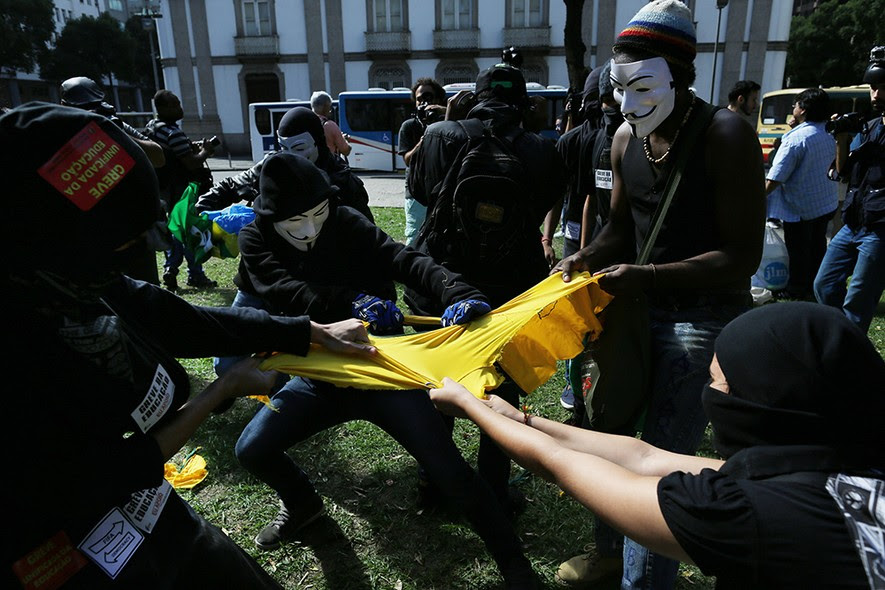 Manifestantes mascarados rasgam camiseta da SELEÇÃO BRASILEIRA em protesto no centro do Rio de Janeiro
