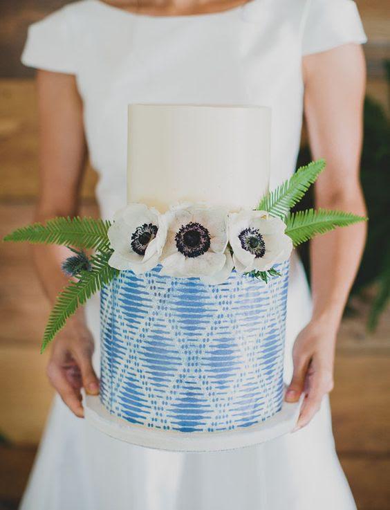 eine Hochzeitstorte mit einer cremigen Schicht und eine gemusterte indigo, garniert mit Blüten