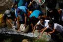 Desperate Venezuelans swarm sewage drains in search of water