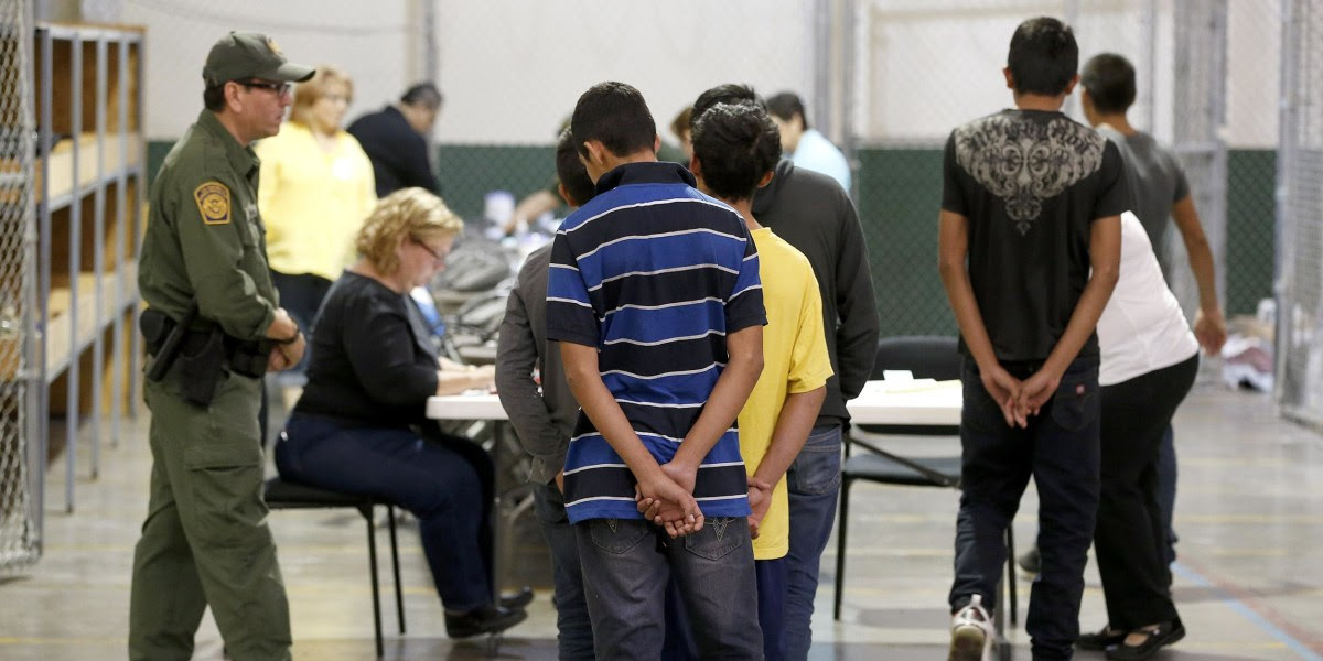 Boys wait in line to make a phone call as they are joined by hundreds of mostly Central American immigrant children that are being processed and held at the U.S. Customs and Border Protection Nogales Placement Center in Nogales
