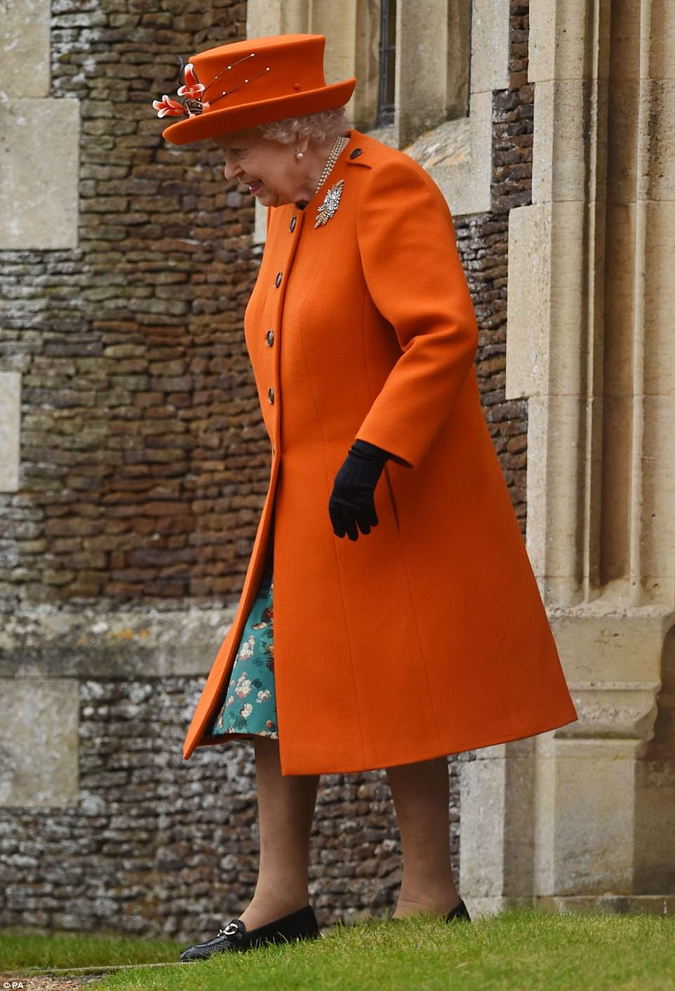 The Queen gave onlookers a peep of her teal floral dress as her bright orange coat gently parted while she strode forward