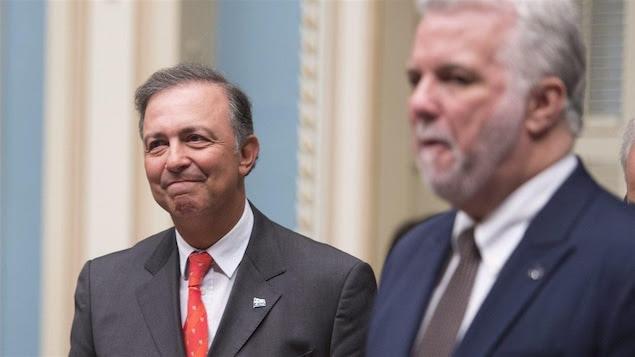 Sam Hamad sourit à l'Assemblée nationale après avoir renoncé à ses privilèges de ministre, le 7 avril 2016. À droite, le premier ministre Philippe Couillard.