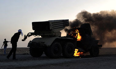 Libyan rebels walk past a burning multi-rocket launcher outside the oil rich town of Ras Lanuf