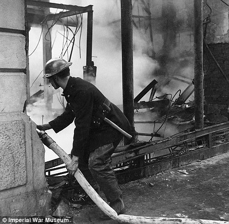 All hands to the pump: A fireman dampens down flames in a bombed building during the Blitz in London in 1940. Four years later, Beaton photographed the Chinese Police force grouped in a circular doorway at headquarters in Chengtu