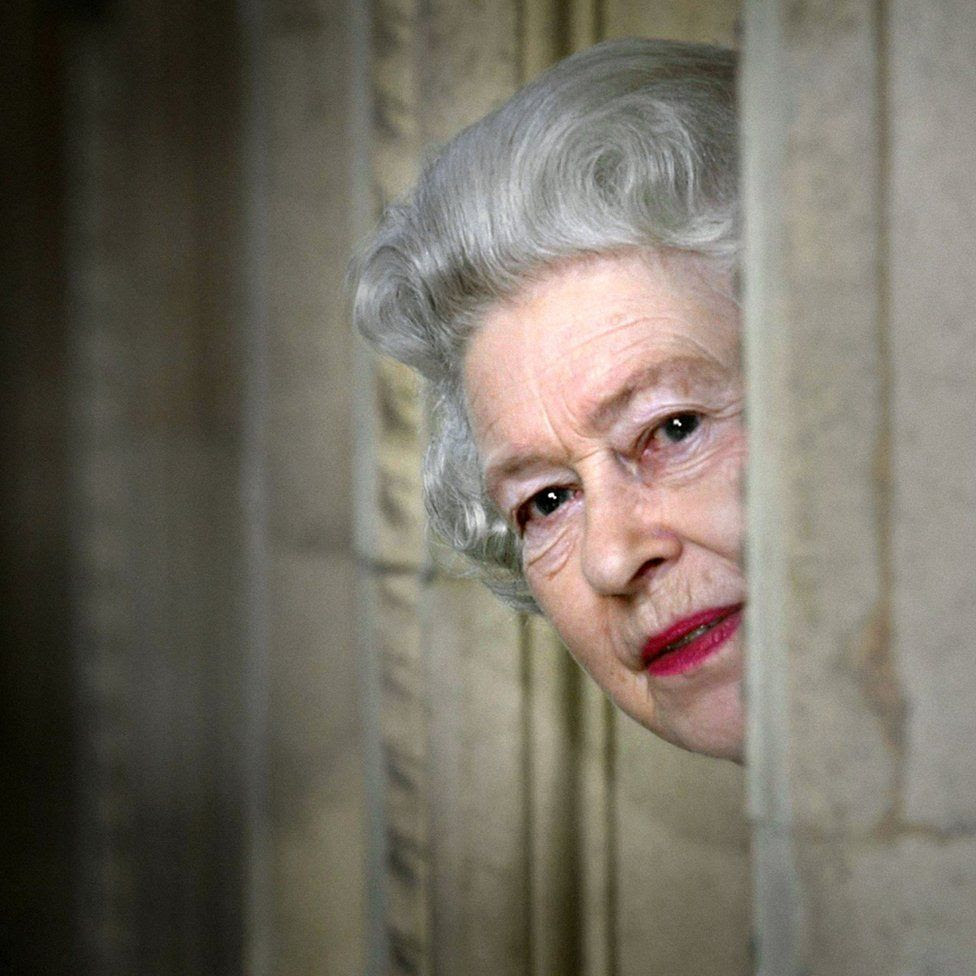 Britain's Queen Elizabeth II peers round a corner during a visit to the Royal Albert Hall in London, marking the end of an eight year restoration program